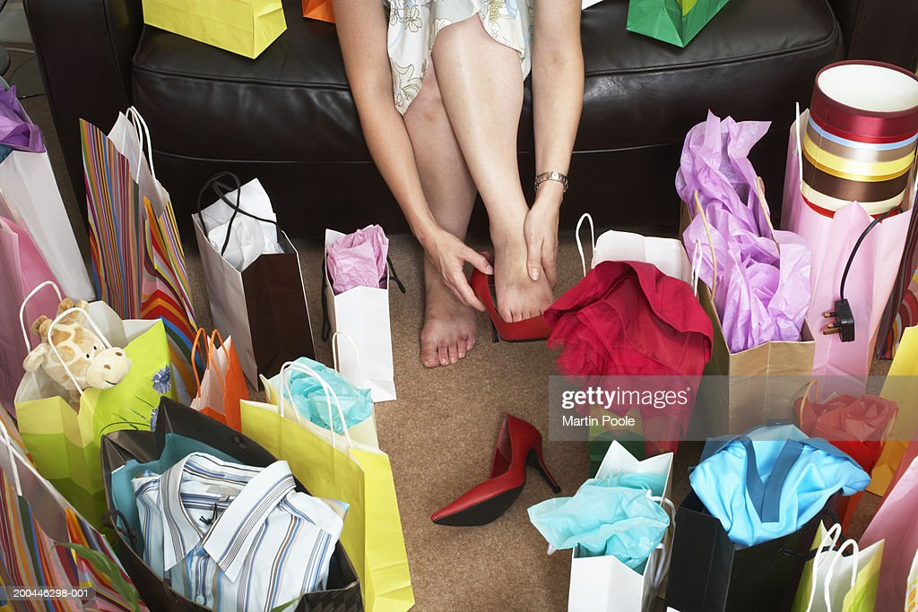 Woman sitting on sofa surrounded with shopping bags, rubbing feet : Stock Photo