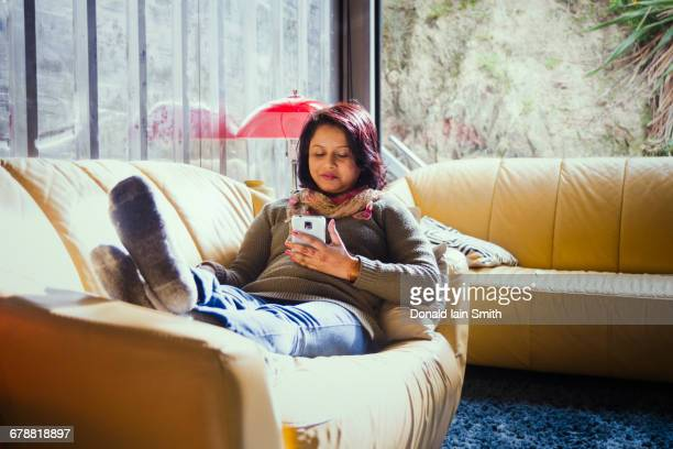 Woman sitting on sofa texting on cell phone
