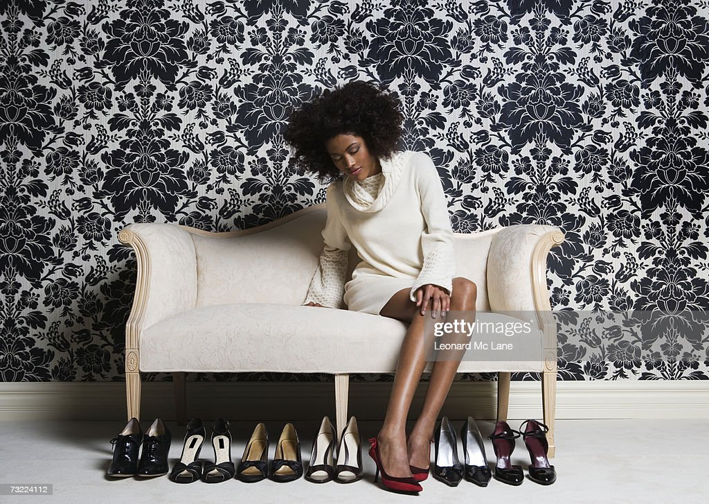 Woman sitting on sofa, trying on shoes : Foto de stock