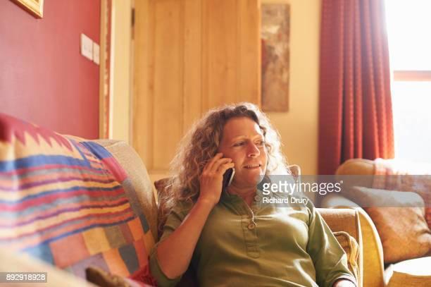 Woman sitting on sofa using phone