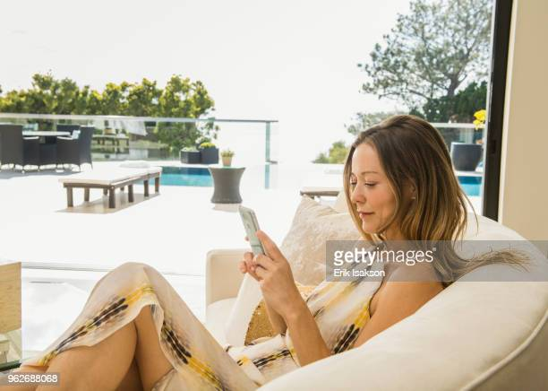 Woman sitting on sofa using smart phone