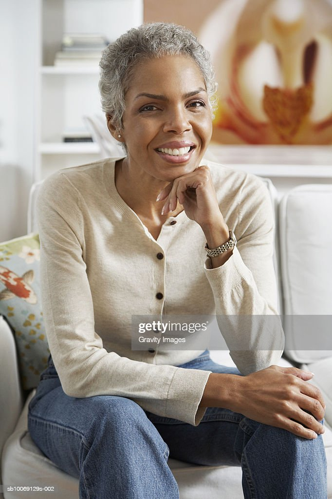 Woman sitting on sofa with hand on chin, smiling, portrait : Stockfoto