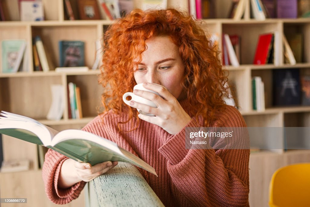Woman sitting on sofa with mug of coffee in bookstore reading a book : Stock Photo