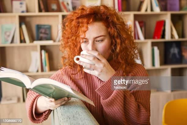 donna seduta sul divano con tazza di caffè in libreria a leggere un libro - legge foto e immagini stock