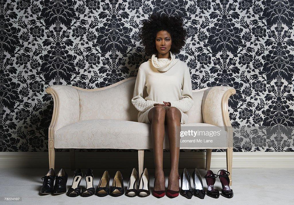 Frau sitzt auf sofa mit passenden Paar Schuhe auf Etage, Porträt : Stock-Foto