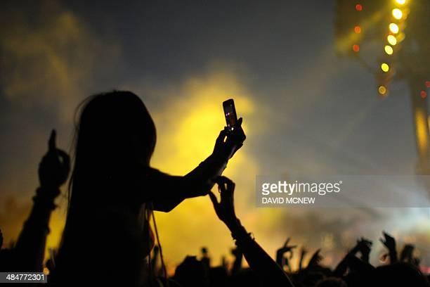 A woman sitting on someone's shoulders is silhouetted against a live image as Arcade Fire performs at the Coachella Valley Music Arts Festival at the...