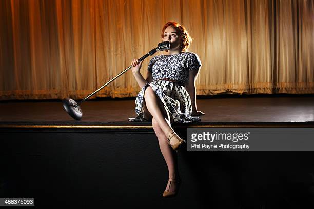 Woman sitting on stage and singing