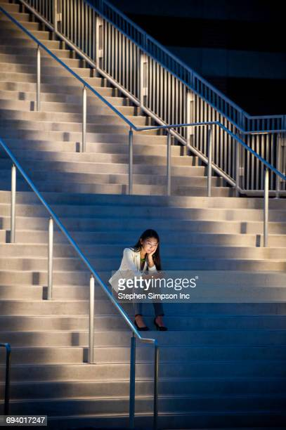 Woman sitting on staircase texting on cell phone
