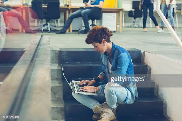 Woman Sitting on stairs and using her laptop.