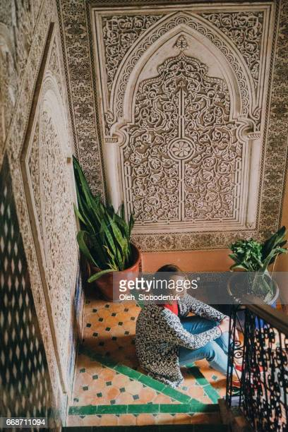 Woman sitting on stairs in riad