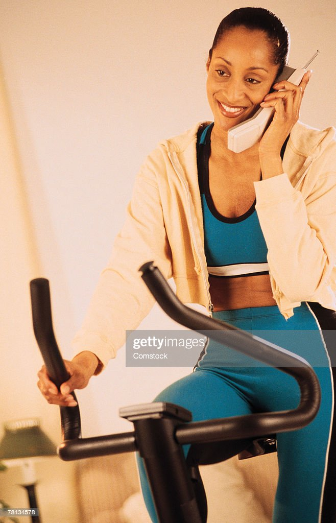Woman sitting on stationary bike on telephone : Stockfoto