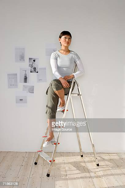 woman sitting on stepladder - step ladder stock photos and pictures