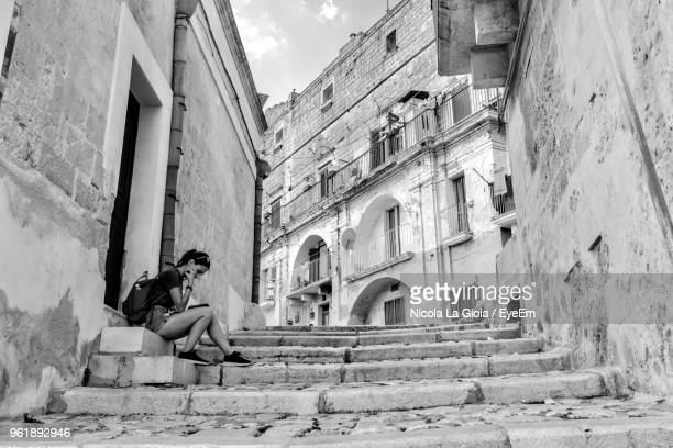 woman sitting on steps against buildings in city - one young woman only stock pictures, royalty-free photos & images