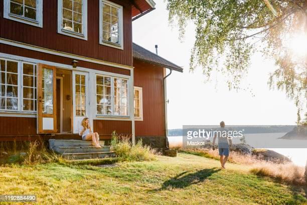 woman sitting on steps at entrance of log cabin while man walking towards lake on sunny day - front view bildbanksfoton och bilder