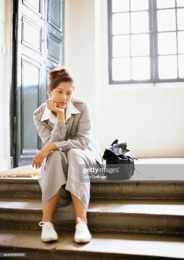 Woman sitting on steps, hand under chin, full length : Stockfoto