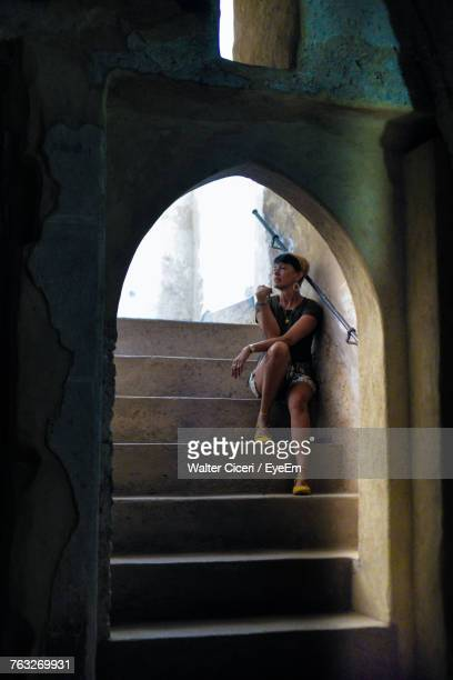woman sitting on steps seen through arch - walter ciceri foto e immagini stock