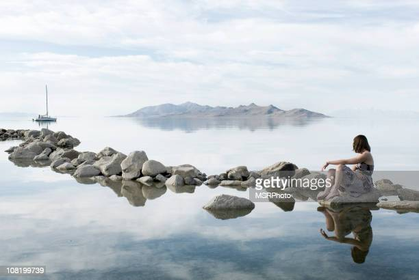 a woman sitting on stones around water daydreaming - great salt lake stock pictures, royalty-free photos & images