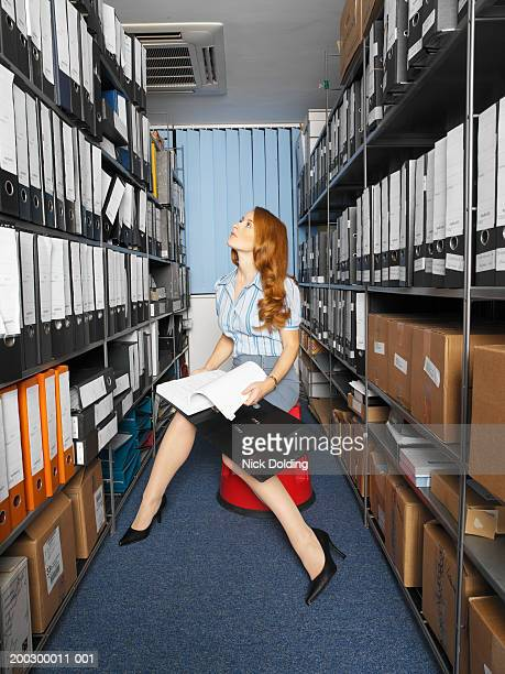 Woman sitting on stool holding file by rows of shelves