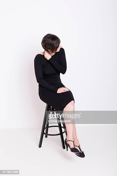 woman sitting on stool looking away