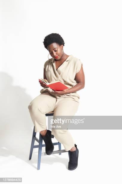 woman sitting on stool reading - businesswear ストックフォトと画像