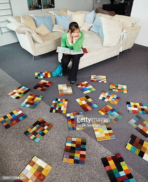 Woman sitting on stool, resting chin on hand looking at carpet samples