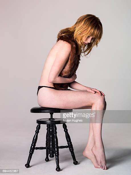 woman sitting on stool wearing fur