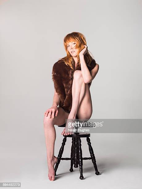 Woman sitting on stool with brown fur around neck