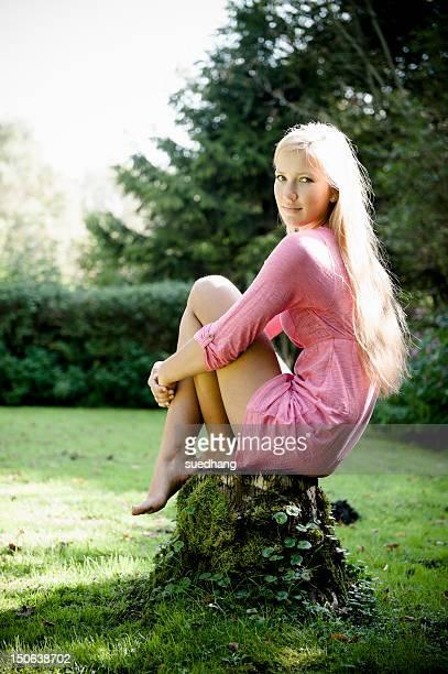 Woman sitting on stump outdoors