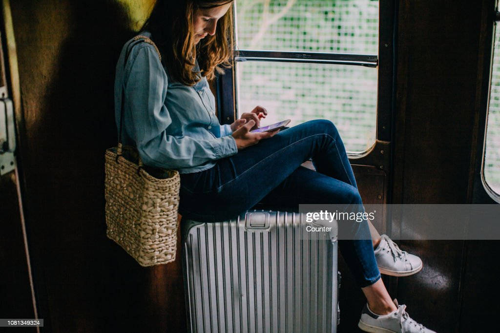 Woman sitting on suitcase in train looking at smart phone : Stock Photo