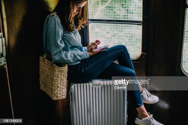 woman sitting on suitcase in train looking at smart phone - reizen stockfoto's en -beelden
