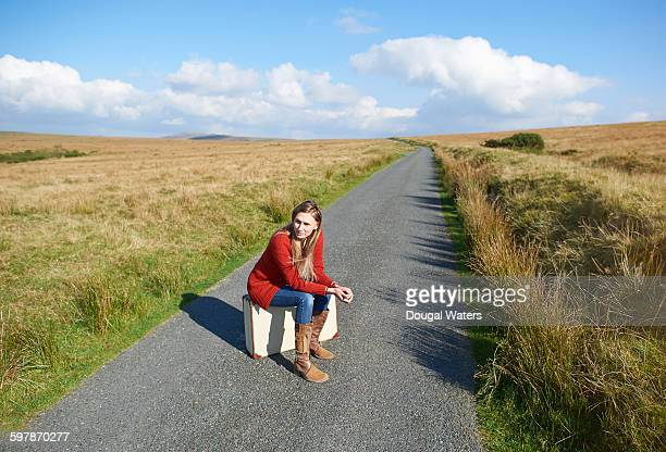 Woman sitting on suitcase on country road.