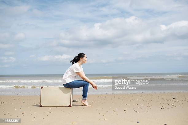 woman sitting on suitcase, waiting at beach. - hand on knee stock pictures, royalty-free photos & images