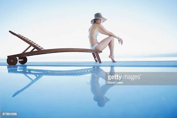 woman sitting on sun lounger by swimming pool - cadeira recostável - fotografias e filmes do acervo