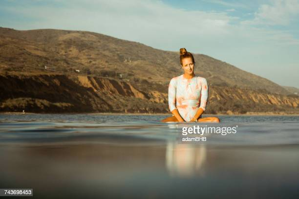 woman sitting on surfboard in ocean, california, america, usa - wading stock pictures, royalty-free photos & images