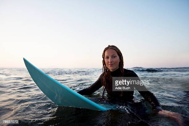 Woman sitting on surfboard in the water.