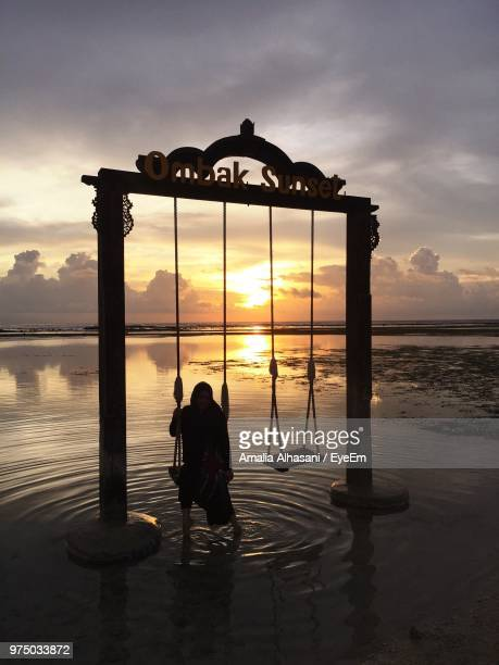 woman sitting on swing over sea against cloudy sky during sunset - gili trawangan stock photos and pictures