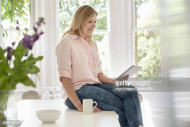 woman sitting on table using digital tablet - fat blonde women stock photos and pictures