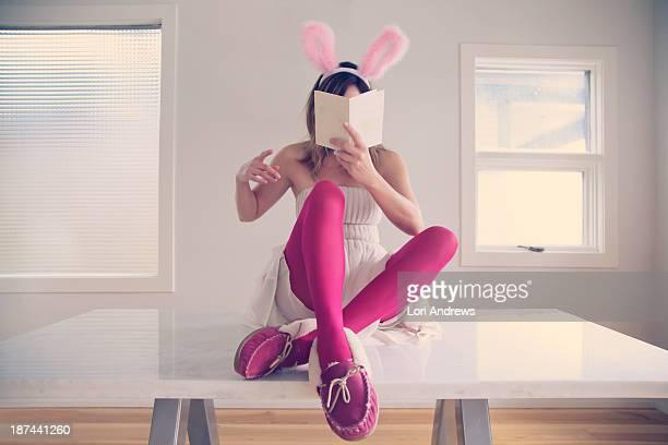 Woman sitting on table wearing bunny ears
