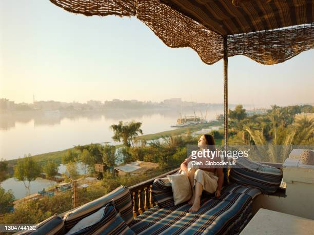 woman sitting on terrace and looking at nile at sunset in luxor - egypt stock pictures, royalty-free photos & images