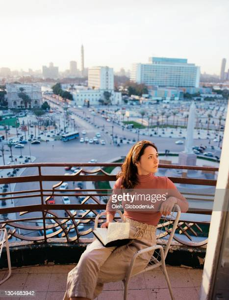 woman sitting on the balcony and looking at view - egypt stock pictures, royalty-free photos & images