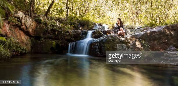 チャパダ・ドス・ヴェデイロス、ゴイアス、ブラジルの小さな滝のそばの小川のほとりに座っている女性 - 30代の女性だけ ストックフォトと画像