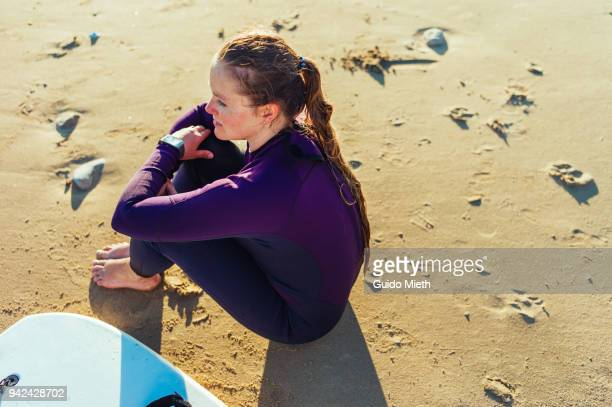 Woman sitting on the beach after surfing.