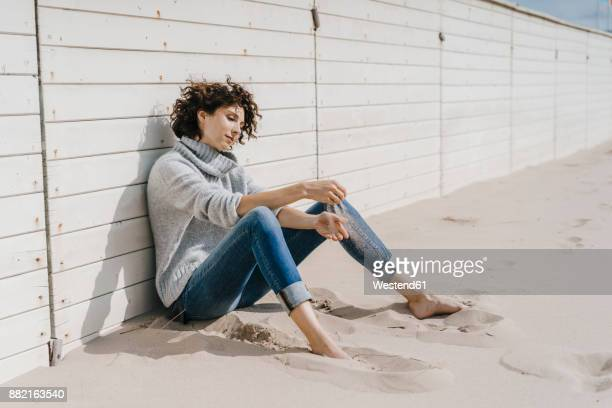 Woman sitting on the beach leaning against wooden wall