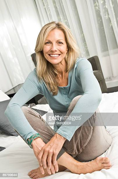 Woman sitting on the bed and smiling