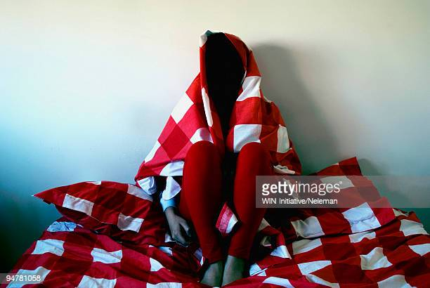 Woman sitting on the bed covered with a red linen, Buenos Aires, Argentina