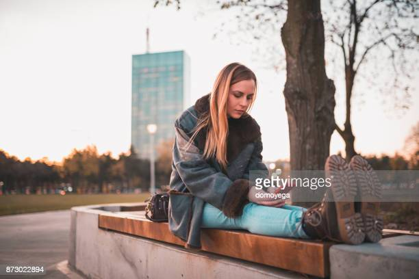 Woman sitting on the bench in the public park and using phone