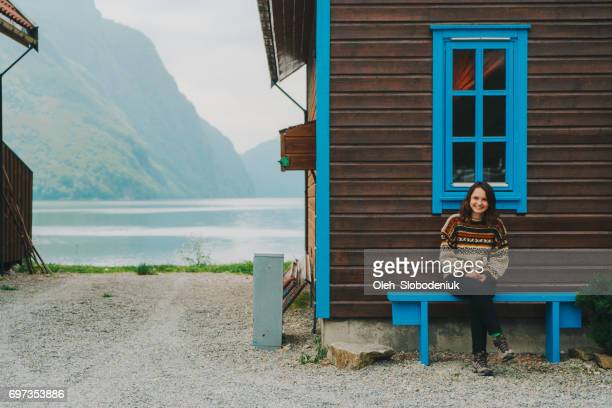 Woman sitting on the bench near the wooden house in Norway