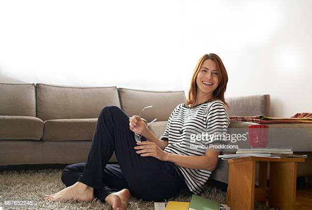 Woman sitting on the carpet and laughing