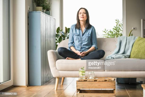 woman sitting on the couch at home with closed eyes - meditieren stock-fotos und bilder