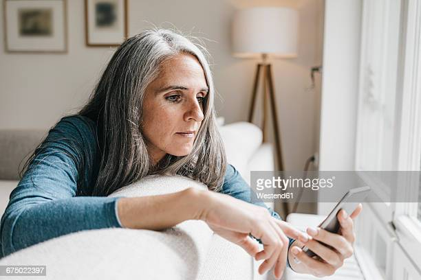 Woman sitting on the couch looking at cell phone
